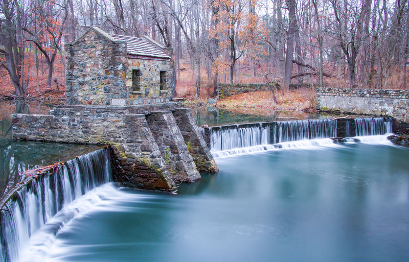 Exterior daytime long exposure stock photo of stone structure sitting atop waterfall on Speedwell Lake in Morristown, New Jersey, Morris County in the fall surrounded by bare trees and leaves on the ground Autumn Daytime Exterior Morris County New Jersey Architecture Built Structure Day Flowing Flowing Water Hydroelectric Power Long Exposure Morristown Morristown Nj Motion Nature No People Outdoors Scenics - Nature Stone Structure Tree Water Waterfall Waterfront