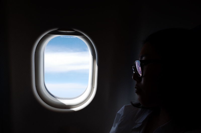 Close-up of woman by airplane window