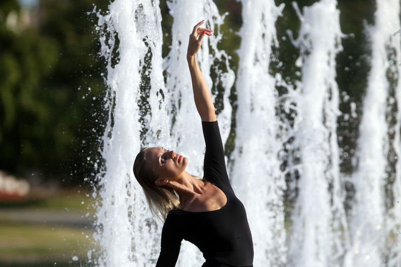 Beautiful woman with hand raised standing against fountain