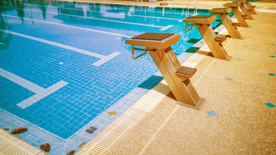 High angle view of chairs in swimming pool