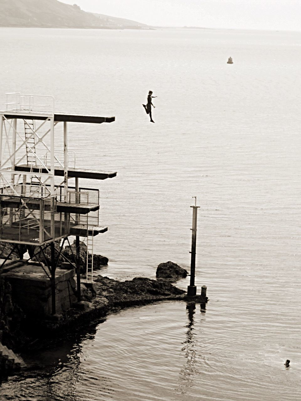 water, sea, nature, men, tranquility, outdoors, full length, real people, tranquil scene, scenics, day, beauty in nature, leisure activity, standing, one person, lifestyles, horizon over water, diving platform, fishing pole, one man only, people