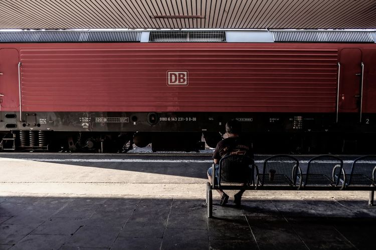 Rear view of man walking on railroad station platform