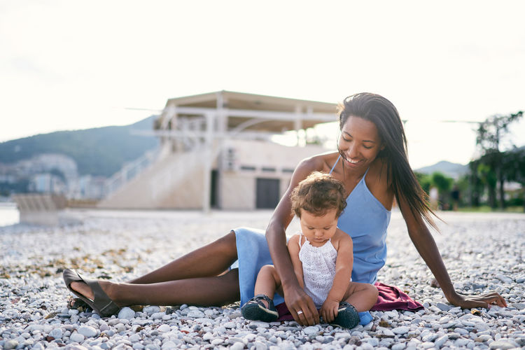 Mother and daughter sitting at beach