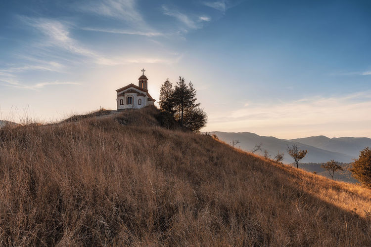 The end of the road, small chapel in Rhodope mountain, Bulgaria near Borovo village House Tree Grass Land Belief Plant Place Of Worship Cloud - Sky Architecture Sun Sunset Nature Church Sky Heaven Spirituality Temple Building Cross Autumn Fall God Field Road Religion Holy Chapel Golden Christianity No People Orange Color Building Exterior Built Structure