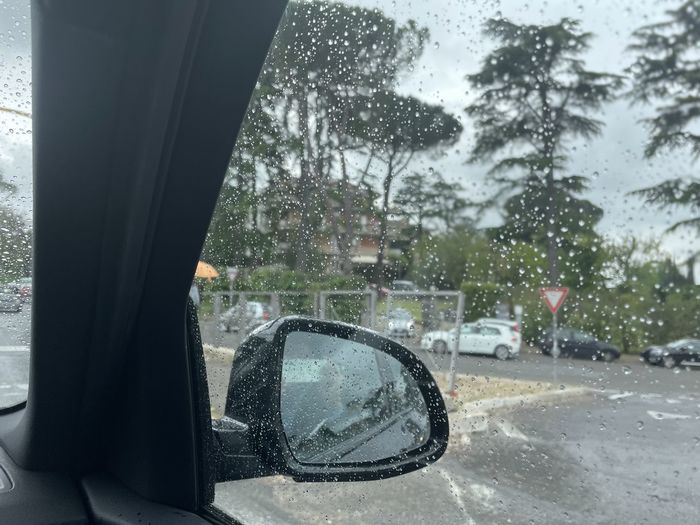 Reflection of side-view mirror on wet window