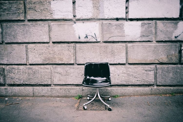 Abandoned chair on footpath against concrete wall