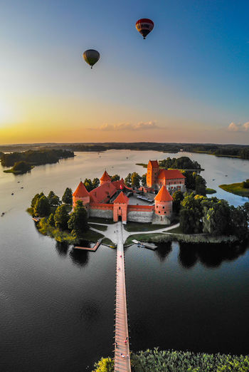 High angle view of castle amidst lake during sunset