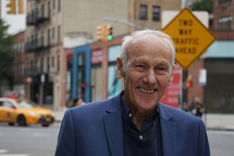 Portrait Of Smiling Senior Man Standing In City