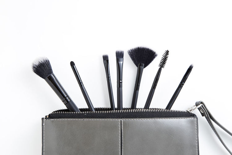 Close-Up Of Make-Up Brushes In Purse Over White Background