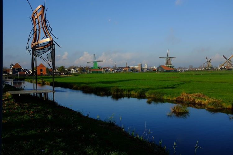 Windmills On Grassy Field Next To Canal
