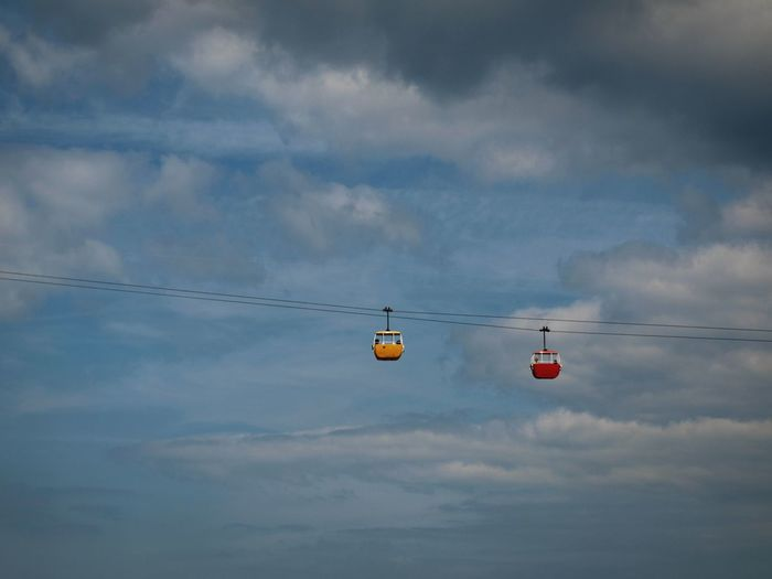 Low Angle View Of Overhead Cable Cars Against Cloudy Sky