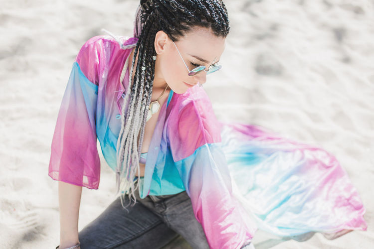 Beautiful expressive fashion forward woman with braided hair laying on the ground Cool Coolin Dressed Up Fashion Hair Hairstyles Sitting Beach Casual Clothing Day Hairstyle Lifestyles Sand Style Sunglasses