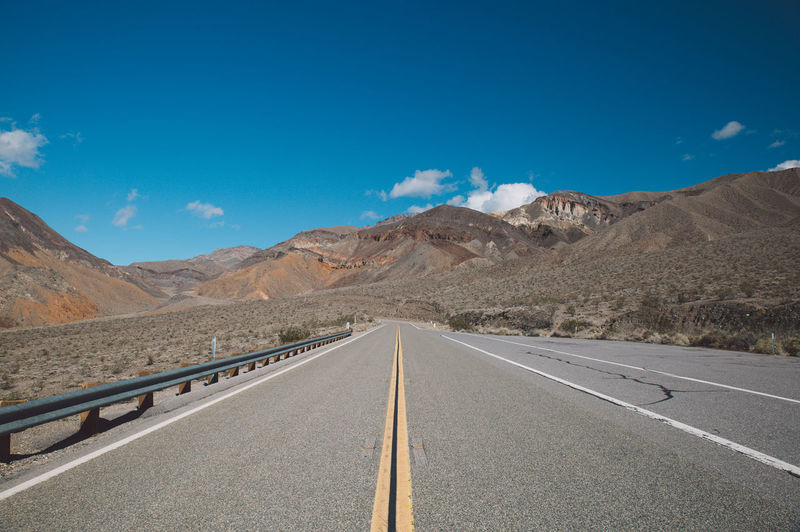 Empty road amidst mountains against blue sky