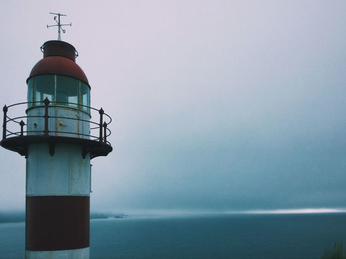 Lighthouse By Lake Against Sky In Foggy Weather