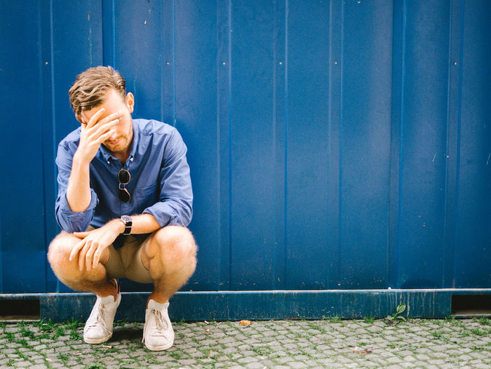 Depressed Man Crouching Against Blue Wall