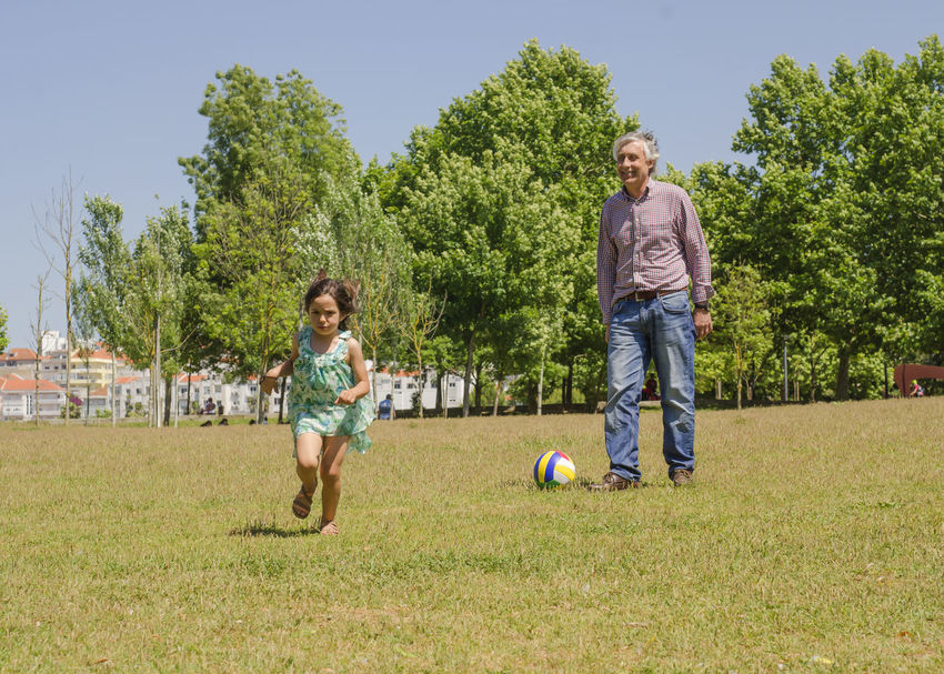 Grandfather and grandson playing with a ball on the city park Bonding Boys Casual Clothing Childhood Day Elementary Age Father Full Length Girls Grandfather And Grandson Grass Growth Leisure Activity Lifestyles Mid Adult Mid Adult Men Outdoors Playing Real People Smiling Soccer Standing Tree Unhappy