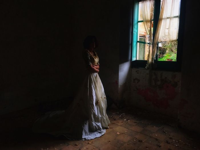 Woman standing on window in abandoned room