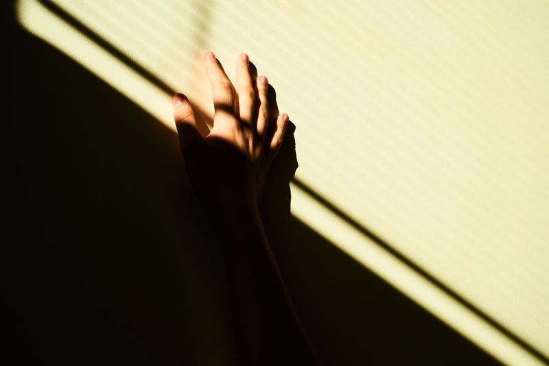Human Body Part Human Hand One Person Hand Indoors  Shadow Body Part Wall - Building Feature Unrecognizable Person Close-up Adult Women Sunlight Real People Finger Light - Natural Phenomenon Human Finger Copy Space Human Limb Dark Minimalism Modern Golden Hour