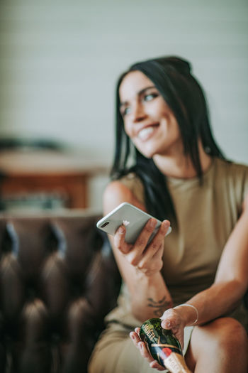 Woman with mobile phone sitting on sofa at home
