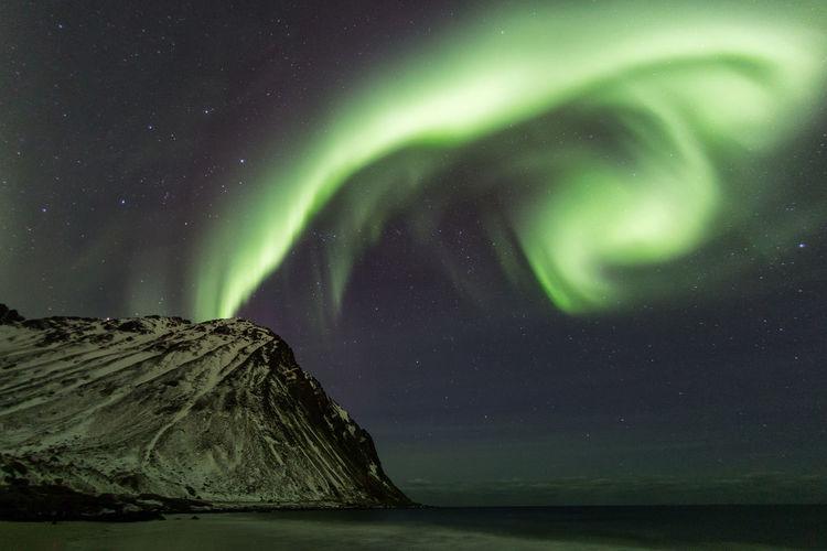 Scenic view of mountain against aurora borealis at night