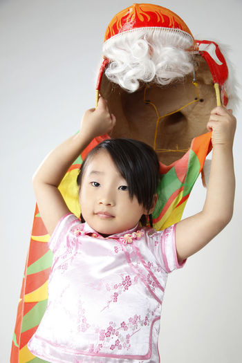 Cute Girl Holding Dragon Costume Against White Background