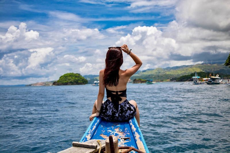 Rear view of woman sitting in boat on sea against sky