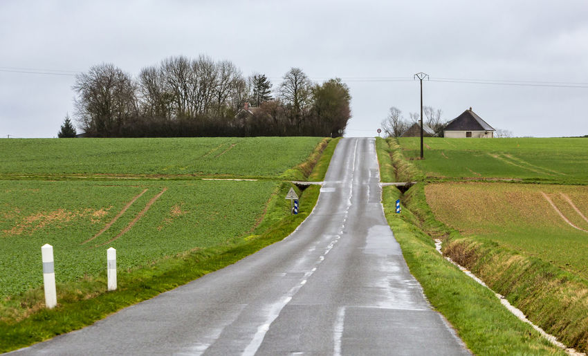 Image of an empty small French countryside road in a cloudy day. Road The Way Forward Direction Transportation Diminishing Perspective No People Nature Land Field Landscape Road Marking Dividing Line Outdoors Asphalt Asphalt Road Countryside Country Road Backgrounds Rural Scene France