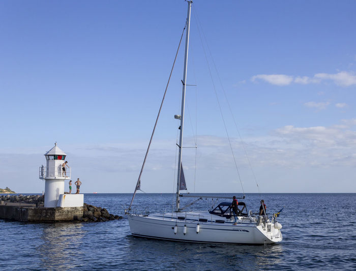 Sailboat by lighthouse Group Of People Lighthouse Nautical Vessel Real People Sailboat Sea Water Waterfront