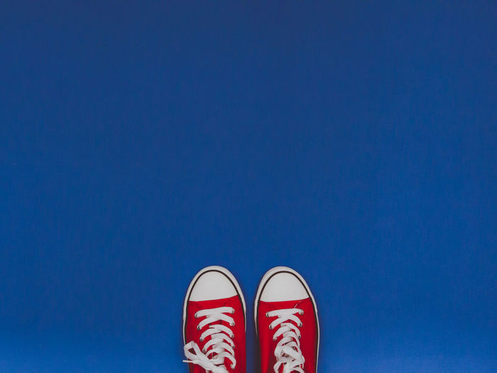 Pair of red sneakers on the blue pastel background. Blue Background Canvas Shoe Clothing Converse Copy Space Fashion Footwear Gym Shoes Hipster Laces Lifestyles Minimalism New Pair Retro Rubber Shoe Shoes Sneakers Studio Shot Vibrant Color Vintage White Youth