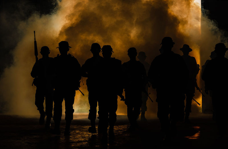Silhouette army soldiers with guns walking by towards smoke