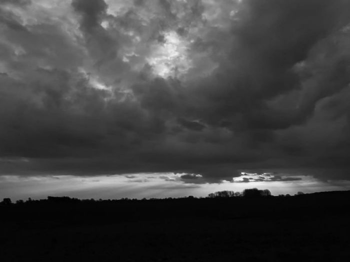 Storm clouds over silhouette landscape