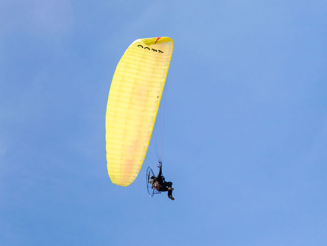 Caesarea, Israel, March 03, 2018 : The sportsman on a color motorized parachute flies in the clear day in the sky above Caesarea in Israel Beautiful Exercise Freedom High RISK Action Adventure Blue Sky Culture Day Extreme Sports Flight Flying Helmet Journey Leisure Activity Motorized Parachute Paragliding Paramotor Powered Propeller Sport Training Vehicle