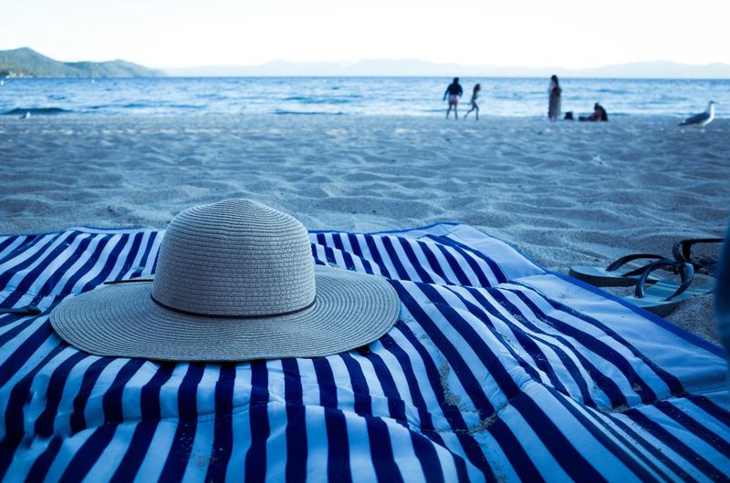 Sun Hat On Striped Blanket At Beach