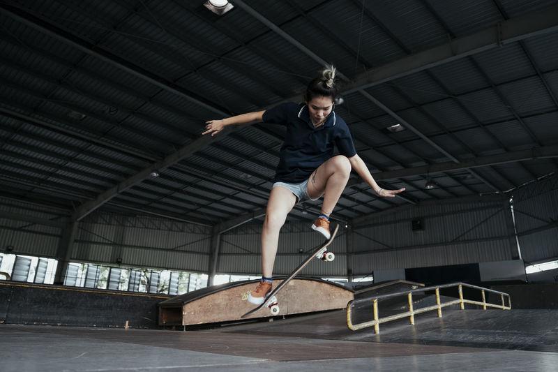 Full length of woman skateboarding on ramp