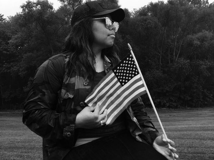 Young Woman Holding American Flag While Sitting At Park
