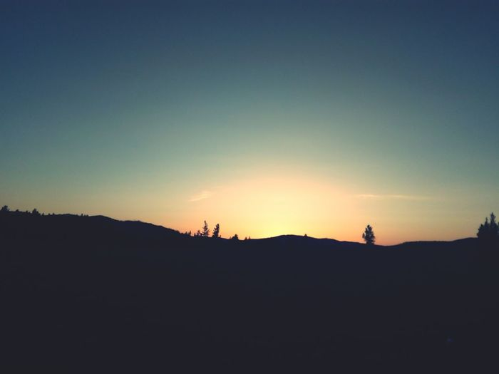Silhouette land against sky during sunset