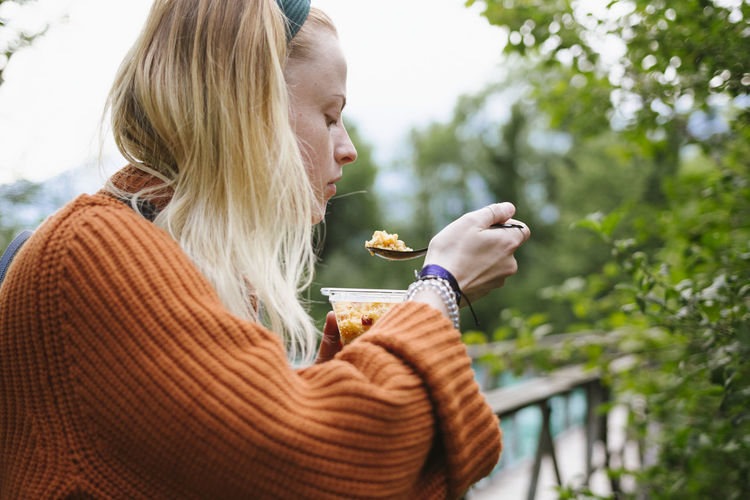 Side view of woman eating food