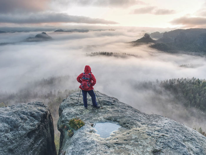 Backpacker stay on wet rock. misty daybreak in rocky mountains. hiker with backpack stand on rock