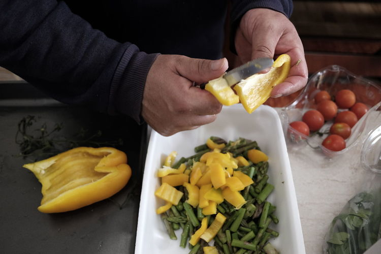 Cropped hand of man chopping yellow bell pepper in kitchen