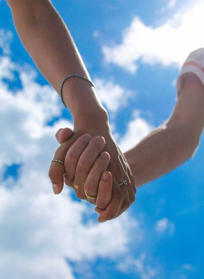 Close-up of couple holding hands against blue sky