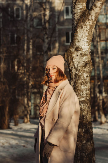 Portrait of woman standing by tree trunk during winter