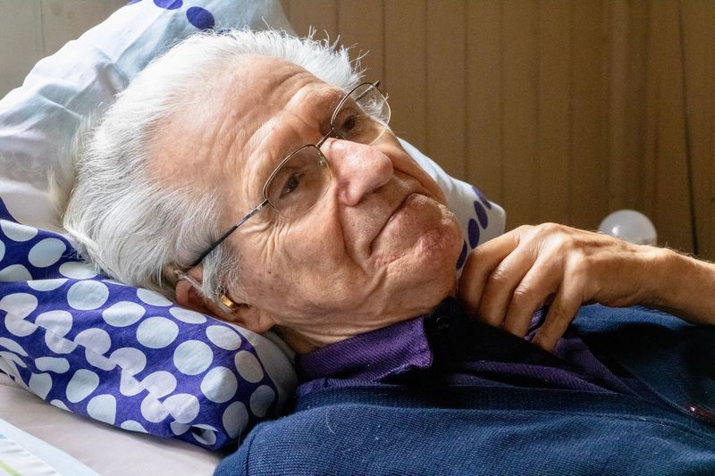 Close-up of senior man relaxing on bed at home