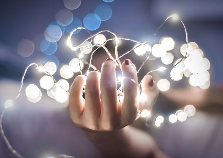 Close-up of woman's hand holding fairy lights