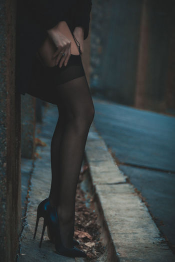 Low section of woman adjusting stockings outdoors