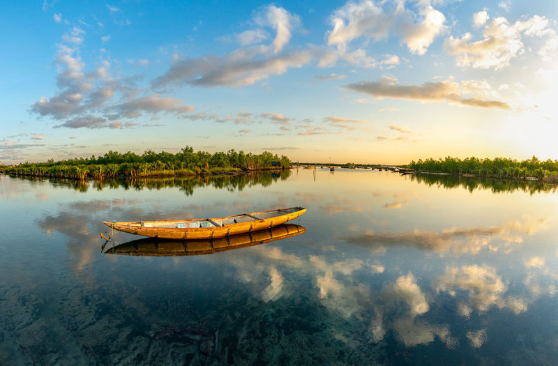 Fishing boat in lake against sky during sunset
