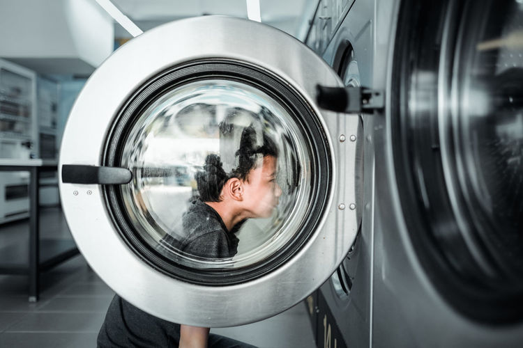 Side View Of Boy Looking At Washing Machine In Laundromat
