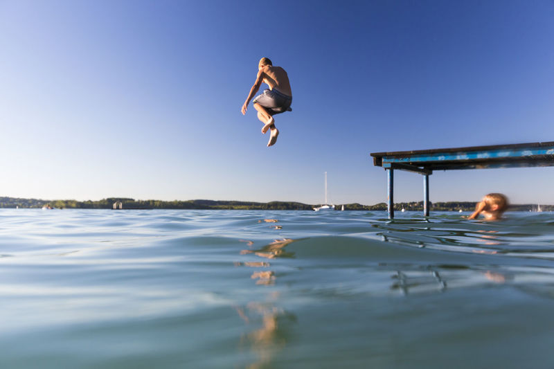 Low angle view of boy jumping into lake against clear blue sky