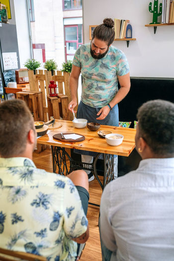 Rear view of people sitting at restaurant table