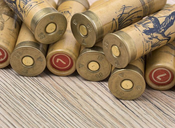 Hunting cartridges of 12 gauge for shotgun on wooden background. Shell; Weapon; Shotgun; Gun; Ammunition; Bullet; Shot; Brass; Cartridge; Metal; Copper; Hunting; Military; Rifle; Danger; Ammo; 12; Fire; Background; War; Violence; Lead; Sport; Power; Gunpowder; Crime; Red; Plastic; Hunt; Isolated; Hunter; Death; Leisure