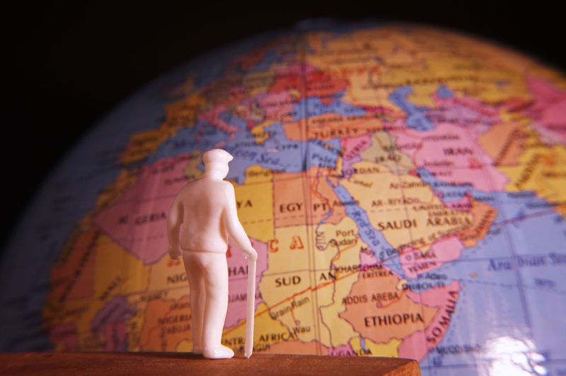 Close-up of figurine on table by globe against black background
